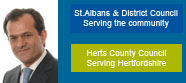 Dursun Portrait. St.ALbans City and District Logo. Hertfordshire County Council Logo